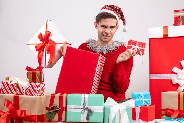 Junger mann der vorderansicht, der viele geschenkboxen hält, die um weihnachtsgeschenke sitzen