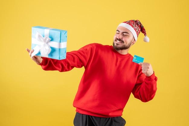 Junger mann der vorderansicht, der weihnachtsgeschenk und bankkarte auf gelbem schreibtisch hält