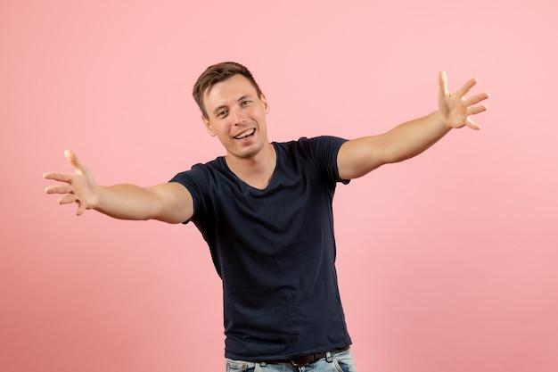 Junger mann der vorderansicht im blauen t-shirt in der begrüßungshaltung auf menschlichem mann des rosa hintergrundemotionsfarbmodells