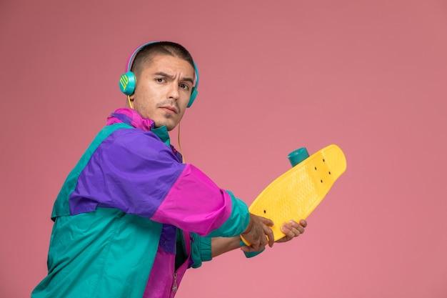 Junger mann der vorderansicht im bunten mantel, der musik hört, die bereit ist, auf rosa schreibtisch zu schlagen