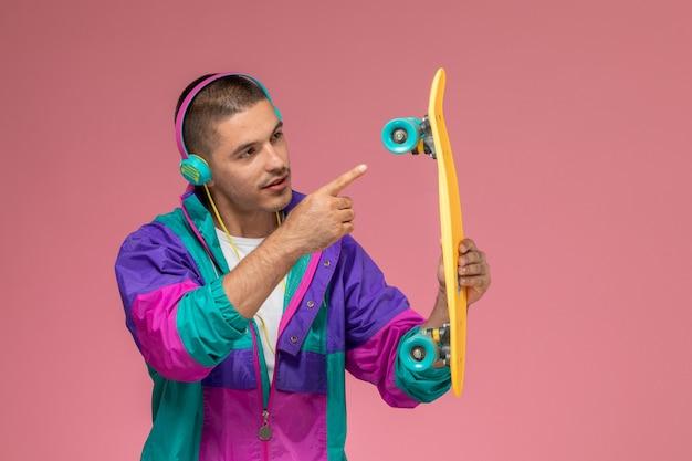 Junger mann der vorderansicht im bunten mantel, der musik hört und skateboard auf hellrosa schreibtisch hält