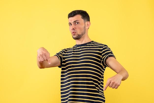 Junger mann der vorderansicht im gestreiften schwarzweiss-t-shirt, das auf den gelben isolierten hintergrund des bodens zeigt