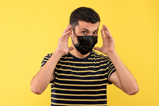 Junger mann der vorderansicht im gestreiften schwarzweiss-t-shirt, das auf gelbem hintergrund steht