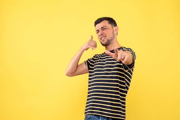 Junger mann der vorderansicht im gestreiften schwarzweiss-t-shirt, das mich zeichen auf gelbem lokalisiertem hintergrund anruft
