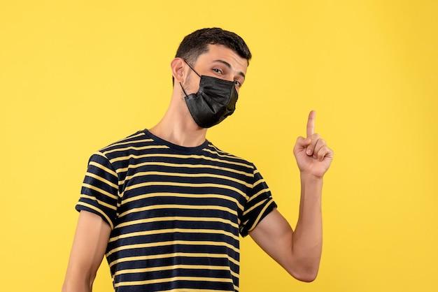 Junger mann der vorderansicht im gestreiften schwarzweiss-t-shirt, das mit dem finger oben auf gelbem lokalisiertem hintergrund zeigt