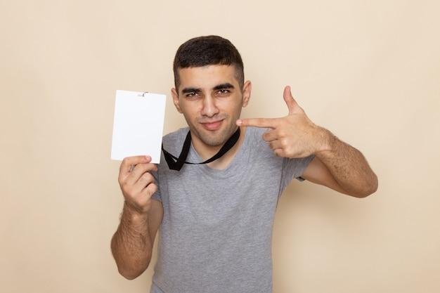 Junger mann der vorderansicht im grauen t-shirt, der ausweis mit hellem lächeln auf beige hält