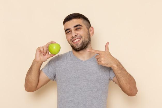 Junger mann der vorderansicht im grauen t-shirt und in den blauen jeans lächelnd und hält grünen apfel auf beige