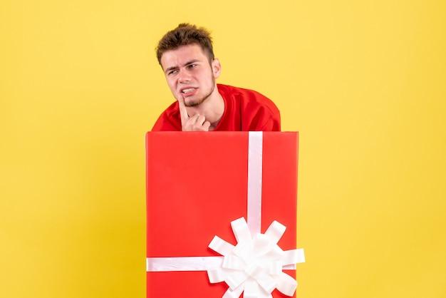 Junger mann der vorderansicht im roten hemd, das innerhalb der gegenwärtigen box steht