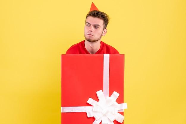 Junger mann der vorderansicht im roten hemd, das innerhalb der gegenwärtigen schachtel sitzt