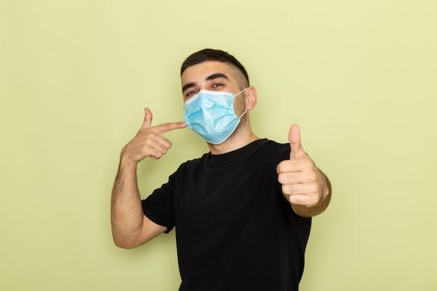 Junger mann der vorderansicht im schwarzen t-shirt, das sterile maske trägt und auf grün aufwirft