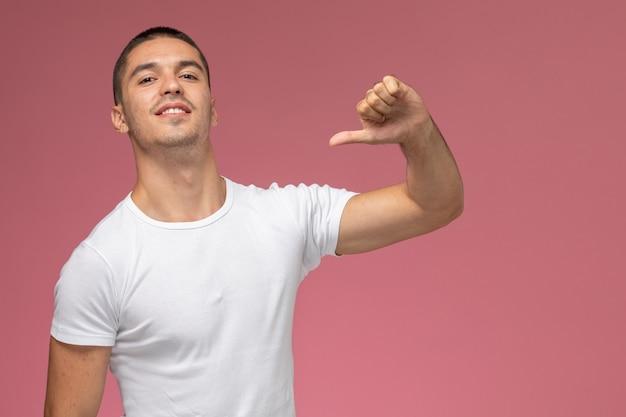 Junger mann der vorderansicht im weißen hemd, das im gegensatz zum zeichen auf rosa hintergrund zeigt