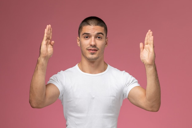 Junger mann der vorderansicht im weißen hemd, das mit seinen händen auf dem rosa hintergrund aufwirft