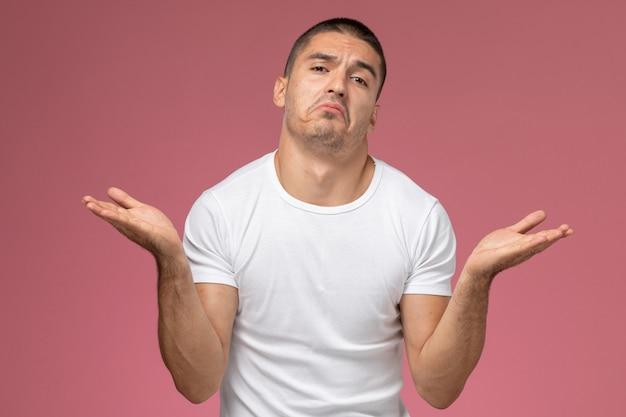 Junger mann der vorderansicht im weißen hemd, das mit verwirrtem ausdruck auf dem rosa hintergrund aufwirft