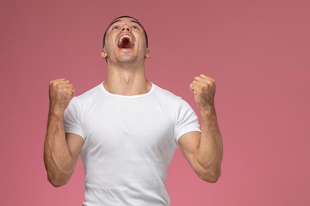 Junger mann der vorderansicht im weißen hemd, das sich emotional auf dem rosa hintergrund freut