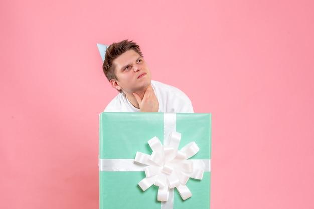 Junger mann der vorderansicht im weißen hemd mit kappe und geschenk, das auf rosa hintergrund nervös ist