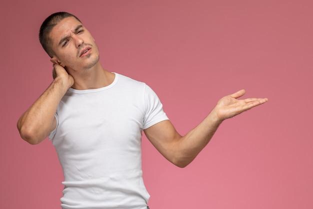 Junger mann der vorderansicht im weißen t-shirt, das einen nackenschmerz auf rosa hintergrund hat