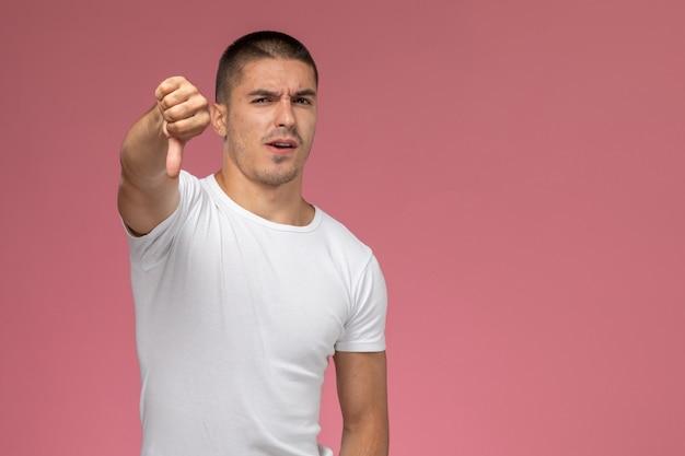 Junger mann der vorderansicht im weißen t-shirt, das im gegensatz zum zeichen auf rosa hintergrund zeigt