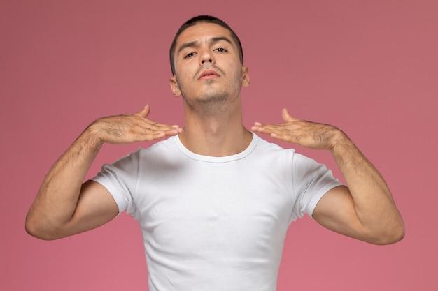Junger mann der vorderansicht im weißen t-shirt, das mit erhabenen händen auf rosa hintergrund aufwirft
