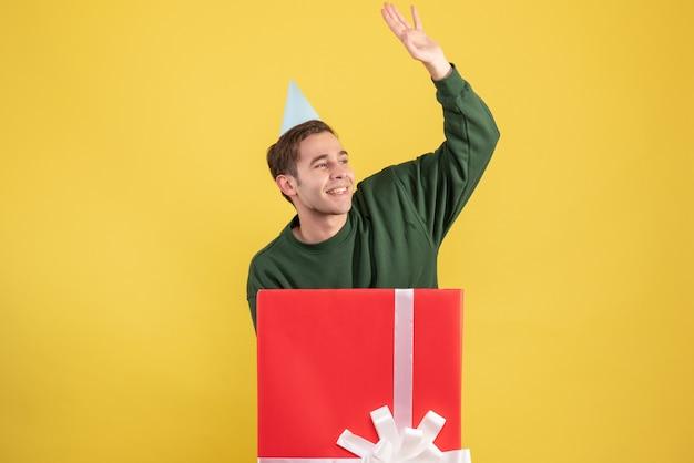 Junger mann der vorderansicht mit der partykappe, die jemanden begrüßt, der hinter der großen geschenkbox auf gelbem hintergrund steht