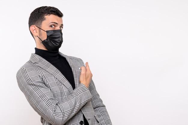 Junger mann der vorderansicht mit der schwarzen maske, die nach hinten zeigt, steht auf freiem raum des weißen isolierten hintergrunds