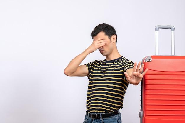 Junger mann der vorderansicht mit gestreiftem t-shirt und koffer, das auge mit hand macht, das stoppschild macht