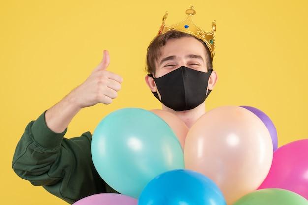 Junger mann der vorderansicht mit krone und schwarzer maske, die daumen auf schild gelb machen