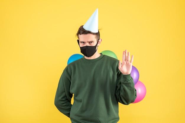 Junger mann der vorderansicht mit parteimütze und bunten luftballons, die jemanden begrüßen, der auf gelb steht