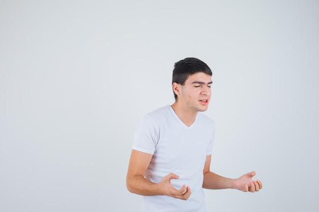 Junger mann, der vorgibt, etwas im t-shirt zu fangen und fröhlich auszusehen. vorderansicht.