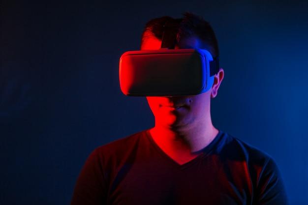 Junger mann, der vr-kopfhörer trägt und virtuelle realität erlebt.