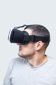 Junger mann, der vr kopfhörer, virtuelle realität erfahrend verwendet