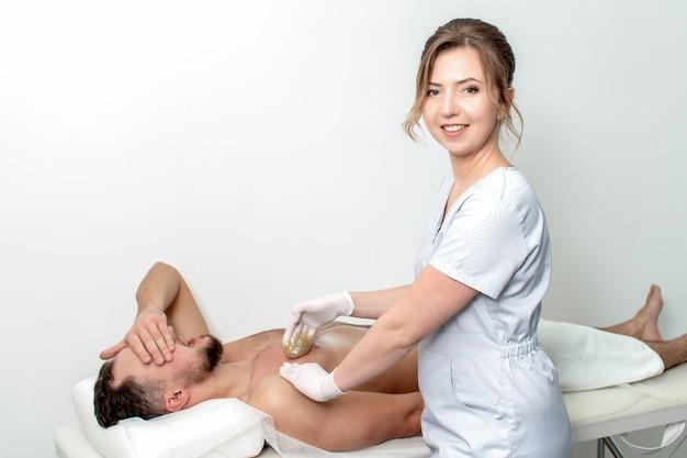 Junger mann, der wachsende brust durch junge weibliche kosmetikerin im schönheitssalon erhält. porträt der jungen weiblichen kosmetikerin während des wachsens der männlichen brust