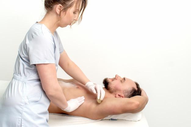 Junger mann, der wachsendes achsel oder epilationsarm von junger weiblicher kosmetikerin im schönheitssalon erhält