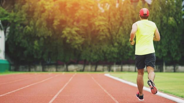 Junger mann, der während des sonnigen morgens auf stadionbahn läuft