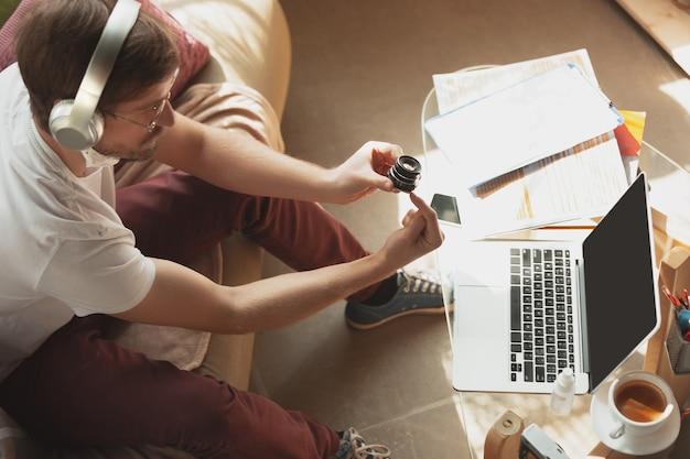 Junger mann, der während online-kursen für fotografen, studioassistenten zu hause lernt.