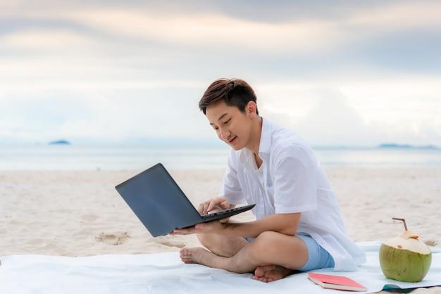 Junger mann, der während seiner ferienzeit durch laptop im freien arbeitet, während er am schönen strand sitzt. sommer, ferien, urlaub und glückliche menschen im thailand-konzept.