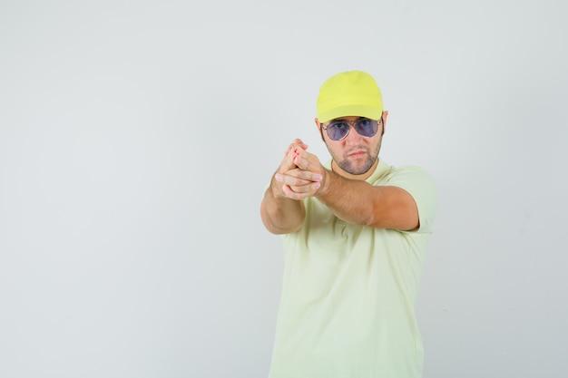 Junger mann, der waffengeste in gelber uniform zeigt und boshaft aussieht.