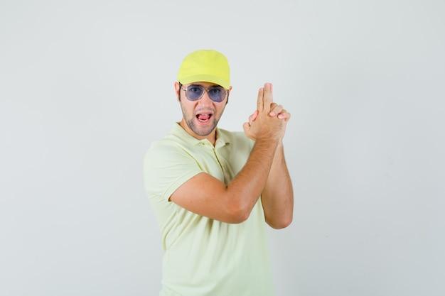 Junger mann, der waffengeste in gelber uniform zeigt und selbstbewusst aussieht.