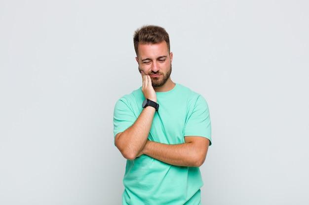 Junger mann, der wange hält und schmerzhafte zahnschmerzen leidet, sich krank, elend und unglücklich fühlt und einen zahnarzt sucht
