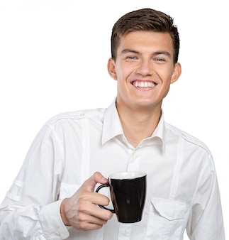 Junger mann, der warme tasse tee / kaffee hält