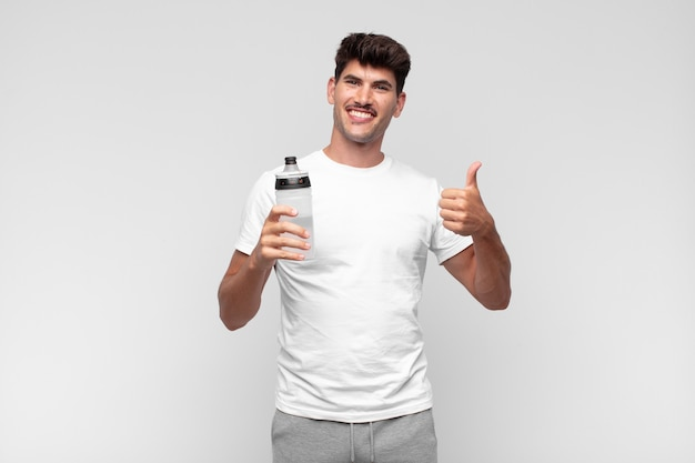 Junger mann, der wasser trinkt und daumen aufgibt