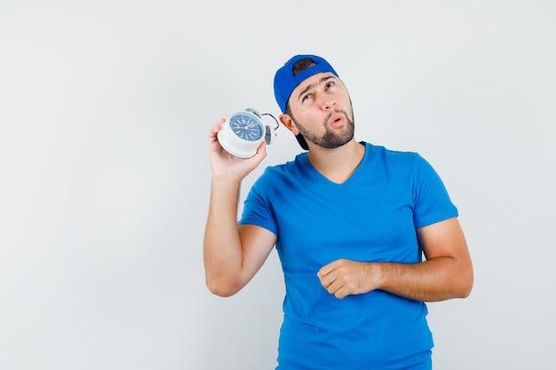 Junger mann, der wecker hält, um lärm im blauen t-shirt und in der vorderansicht der kappe zu hören.