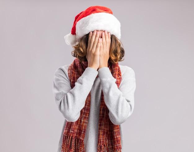 Junger mann, der weihnachtsweihnachtsmütze mit warmem schal um seinen hals trägt gesicht mit händen bedeckt