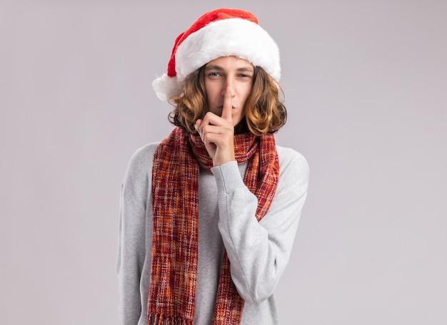 Junger mann, der weihnachtsweihnachtsmütze mit warmem schal um seinen hals trägt und stille geste mit finger auf lippen macht
