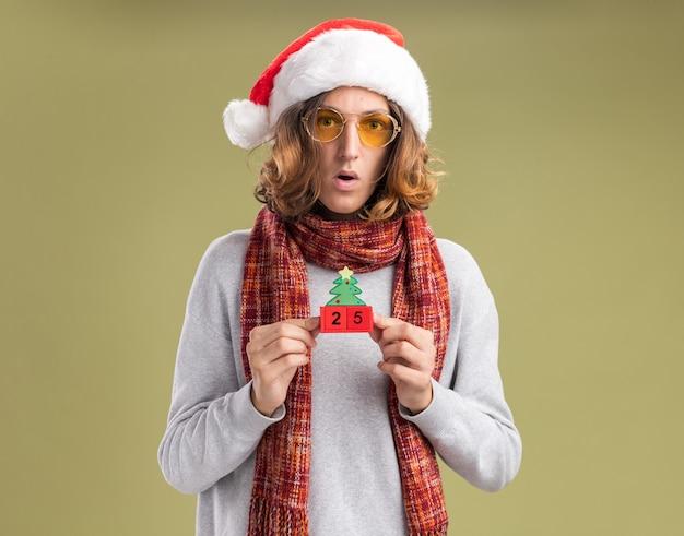 Junger mann, der weihnachtsweihnachtsmütze und gelbe brille mit warmem schal um seinen hals trägt, der spielzeugwürfel mit datum fünfundzwanzig betrachtet kamera verwirrt und überrascht über grünem hintergrund stehend