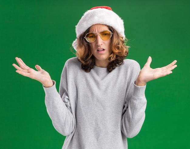 Junger mann, der weihnachtsweihnachtsmütze und gelbe brille trägt, die kamera verwirrte achselzuckenschultern betrachten, die keine antwort über grünem hintergrund stehen