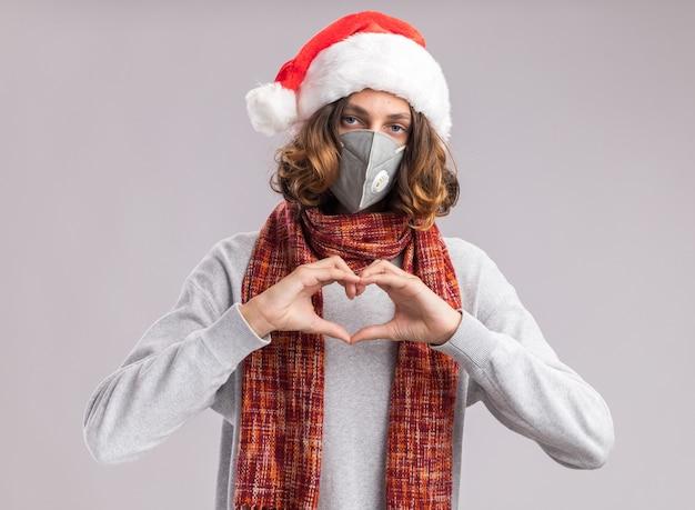 Junger mann, der weihnachtsweihnachtsmütze und gesichtsschutzmaske mit warmem schal um seinen hals trägt und herzgeste mit fingern macht