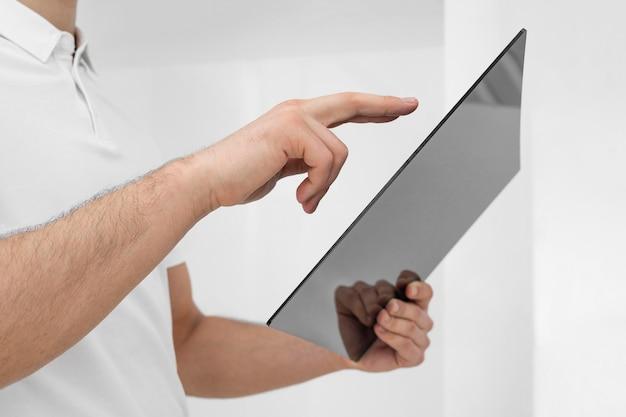 Junger mann, der weiße kleidung mit tablette nahaufnahme trägt