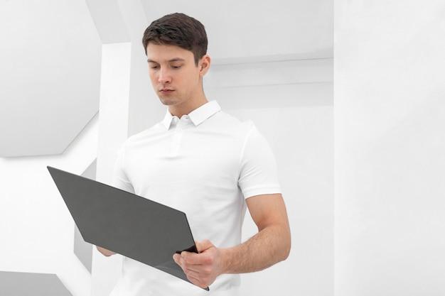 Junger mann, der weiße kleidung mit tablette trägt