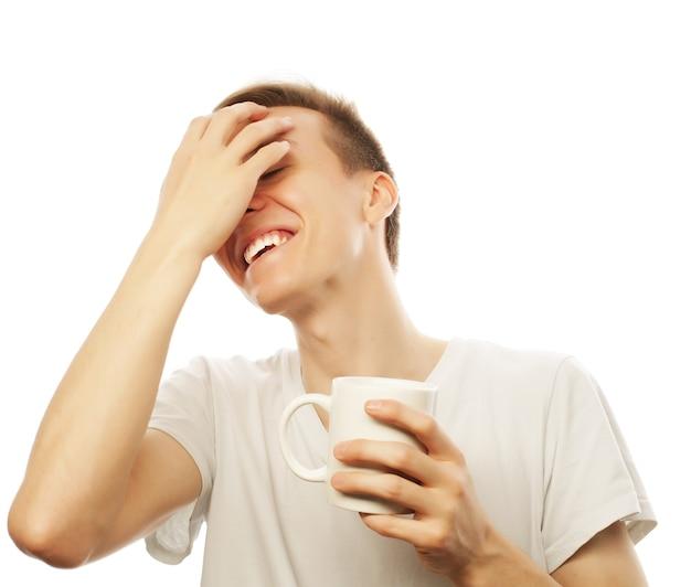 Junger mann, der weiße tasse mit kaffee hält holding