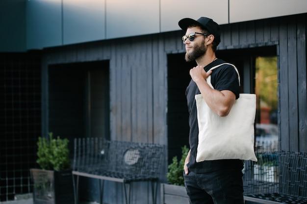 Junger mann, der weiße textilöko-tasche gegen städtischen stadthintergrund hält. ökologie- oder umweltschutzkonzept. weiße öko-tasche zum mock-up.